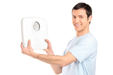 scale model: A happy young man holding a weight scale isolated on white background