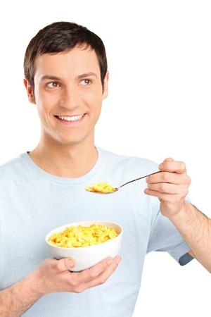 hombre comiendo: Un hombre joven que comer copos de ma�z aislados en fondo blanco