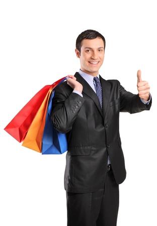 positivismo: Un hombre feliz celebraci�n de bolsas de compra y dando pulgar arriba aislado sobre fondo blanco Foto de archivo