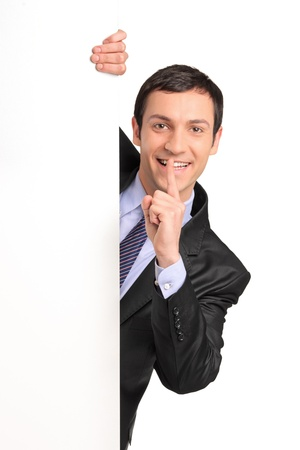 Businessman in a suit gesturing silence with his finger over his mouth, behind white panel, isolated on white background photo
