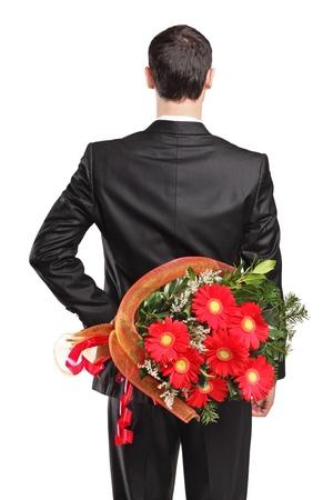 tuxedo man: Uomo indossa il costume nero nascondere un bouquet di fiori dietro la schiena isolato su sfondo bianco