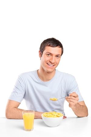 hombre comiendo: Un sonriente copos de ma�z joven comiendo en el desayuno aisladas sobre fondo blanco