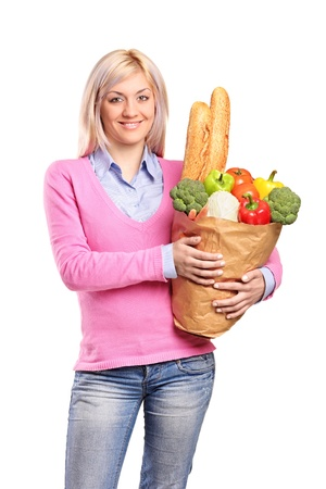 Smiling woman holding a bag filled with bread and vegetables isolated on white background photo