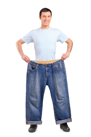 weight loss man: Full length portrait of a weight loss male showing his old jeans isolated on white