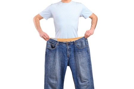 Weight loss male showing his old jeans isolated on white photo