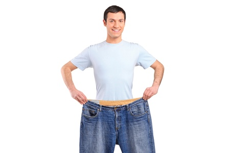 Portrait of a weight loss male showing his old jeans isolated on white photo