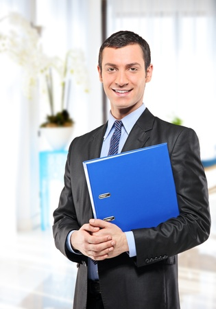 proffesional: A happy businessman with blue folder posing in the office