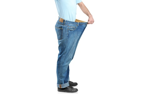 Male showing his lost weight by putting on an old jeans photo