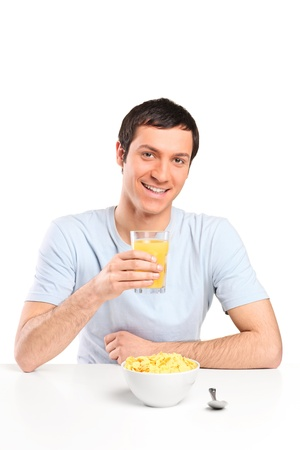 Good looking man having breakfast with orange juice and a bowl of cereal. Isolated on white photo