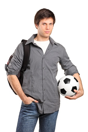 A young school boy carrying a school bag and holding a football isolated on white background Stock Photo - 8926668