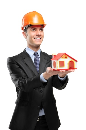 A smiling foreman wearing helmet and holding a model house isolated on white background photo