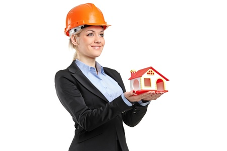 A smiling forewoman wearing helmet and holding a model house isolated on white background photo