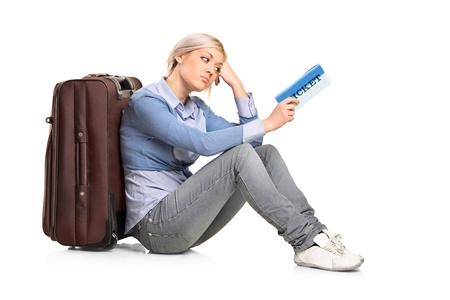 A tourist girl sitting near a suitcase with a ticket in her hand isolated on white background photo