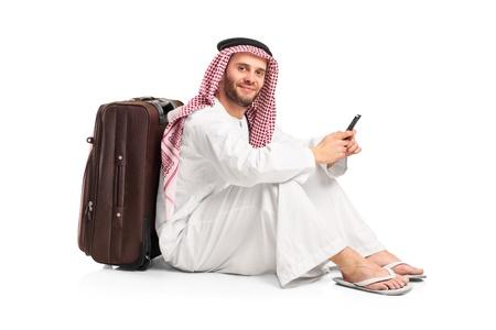 hombre arabe: Hombre �rabe sentado cerca de una maleta y escribiendo un mensaje de texto en su tel�fono celular aislada sobre fondo blanco