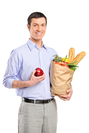 Smiling man holding an Apple, a bag full with bread and vegetables isolated on white background photo