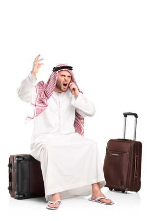 irritated: A furious arab shouting on a mobile phone seated on his luggage isolated on white background
