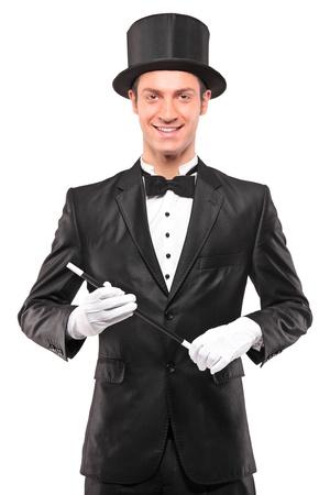 Un mago con una varita mágica y posando aislaron sobre fondo blanco