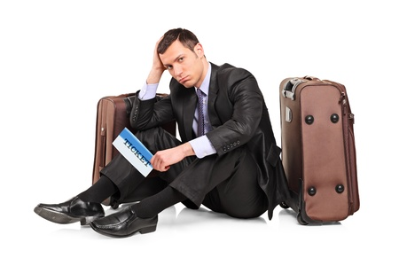 business traveler: A sad business traveler seated next to a suitcase with a ticket in his hand isolated on white background