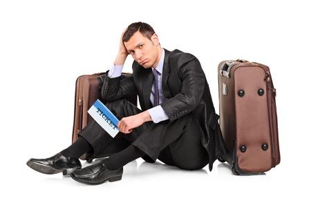 mirada triste: Un viajero de negocios triste sentado junto a una maleta con un boleto en la mano aislado sobre fondo blanco Foto de archivo