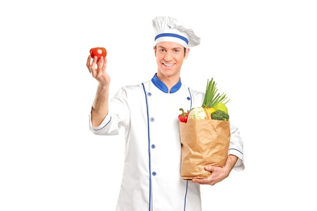 A smiling chef holding a tomato and grocery bag full with vegetables isolated on white background Stock Photo - 8975362