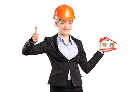 A smiling forewoman holding a model house and giving thumb up isolated on white background photo