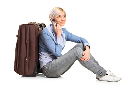 wayfarer: A tourist girl seated next to a suitcase talking on mobile phone isolated on white background