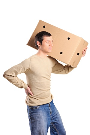 dorsalgia: A young man suffering from back pain while lifting a large box isolated on white background