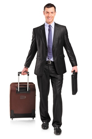 Full length portrait of a business traveler carrying a suitcase isolated against white background photo