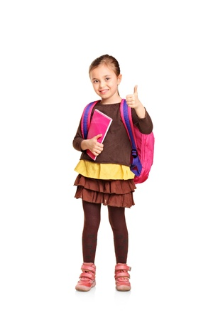 school bags: Full length portrait of a school girl with backpack holding book and showing thumb up isolated on white background Stock Photo