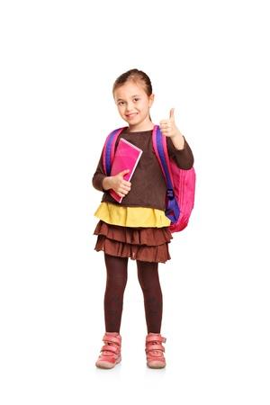 Pleine longueur portrait d'une fille de l'école avec sac à dos tenant livre et montrant le pouce jusqu'à isolé sur fond blanc