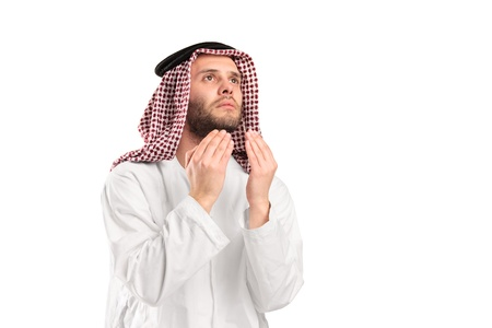 Young arab man of muslim religion praying isolated on white background photo