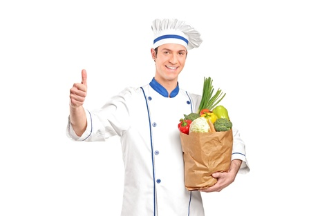 A chef giving thumb up and holding a grocery bag full with vegetables isolated on white background photo