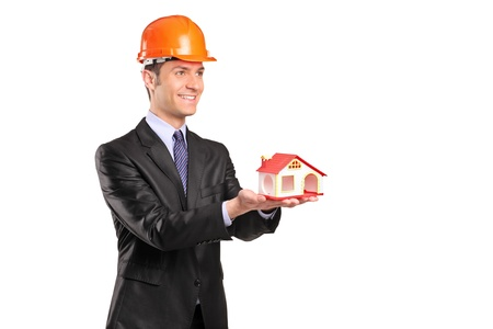 A foreman wearing helmet and holding a model of house isolated against white background photo