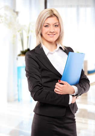 A happy businesswoman with blue folder posing in the office photo