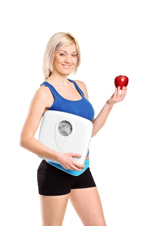 A happy young athlete holding a weight scale and an apple isolated against white background photo