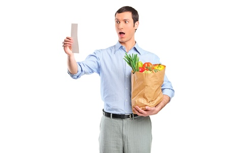 Shocked man looking at store receipt and holding a grocery bag isolated on white background photo