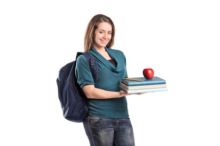 A smiling female student holding books and a red apple isolated on white background photo