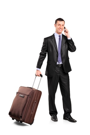 Business traveler carrying a suitcase and talking on a cell phone isolated on white background photo