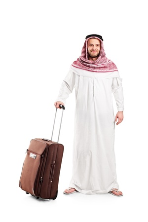 ethnic dress: Full length portrait of an Arab tourist carrying a suitcase isolated against white background Stock Photo