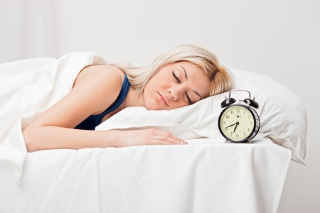 A young sleeping woman and alarm clock in bedroom Stock Photo - 9094140