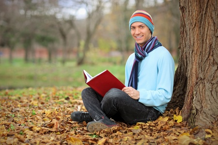 Young smiling man reading a book in the city park in Skopje, Macedonia photo