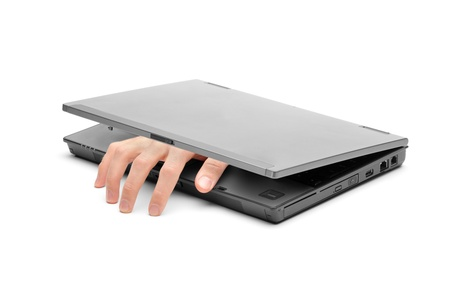 A hand reaching out of a laptop isolated on white background photo