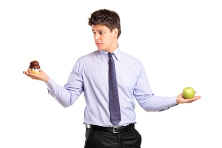 gluttonous: A man holding an apple and slice of cake trying to decide which one to eat isolated on white background