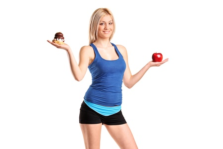 A woman holding an apple and slice of cake trying to decide which one to eat isolated against white background photo