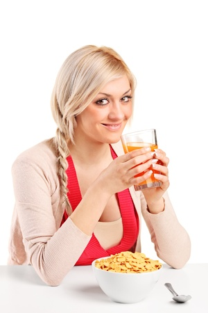 A young female drinking an orange juice and eating cornflakes at breakfast isolated on white background photo