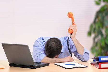 Uitgeput zakenman met de beeldzijde naar beneden houden een telefoon in een kantoor