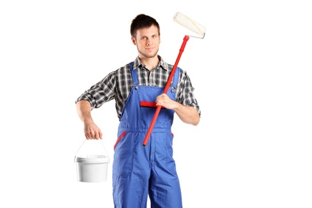 painters: Smiling worker man holding a paint roller and bucket isolated on white background