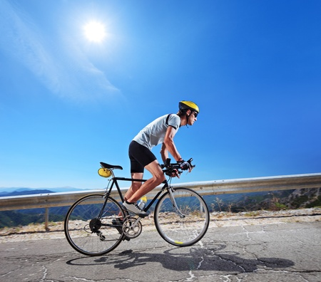 road bike: Cyclist riding a bicycle in Macedonia with a sun in the background