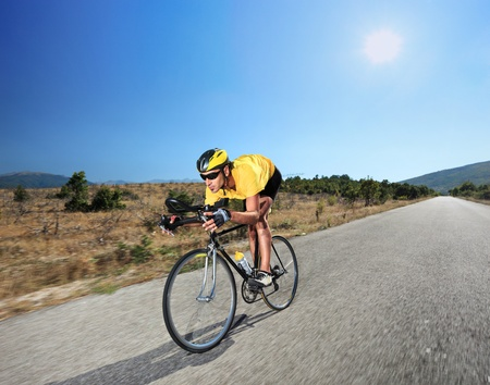 caucasian race: Cyclist riding a bike on an open road in Macedonia with a sun in the background Stock Photo