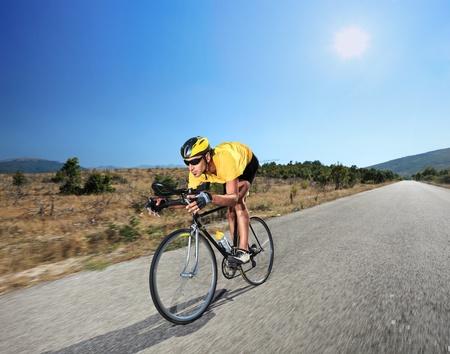cyclist: Fietser met een fiets op een openbare weg in Macedonië met een zon op de achtergrond